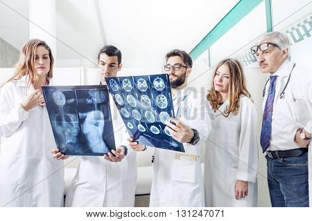 Group Of Doctors Examining An X-ray In Hospital