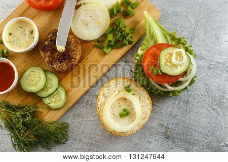 Cooking process of a sandwich burger ingredients on cutting board on wooden table against white background fresh vegetables herbs fried meat buns sauces and knife horizontal top view