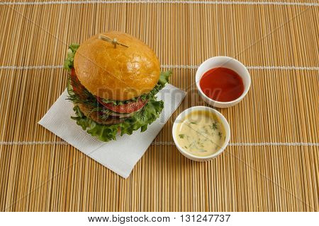 Big beef steak burger with vegetables and herbs and sauces on bamboo placemat horizontal top view