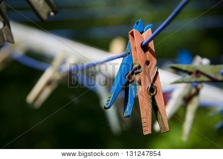 two old dirty plastic clothespins in blue and red hanging side by side on a clothesline selected focus close depth of field