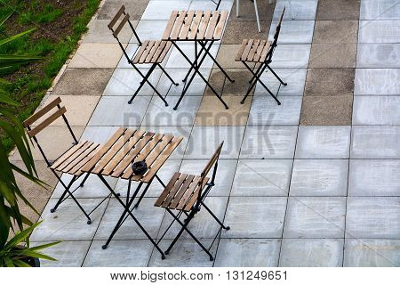 Empty folding chairs and tables on a terrace of concrete slabs in a garden cafe view obliquely from above