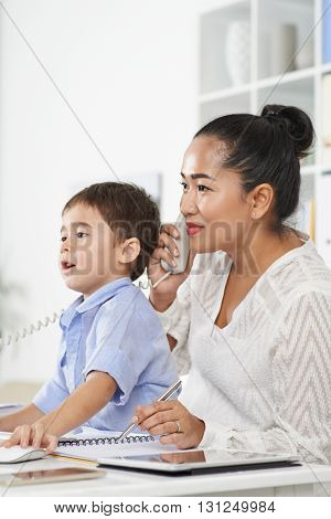 Business lady and her little son looking at computer screen when talking on phone