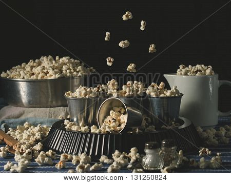 Home made popcorn in alluminium glasses with popcorn in motion on dark background, dark rustic still life.