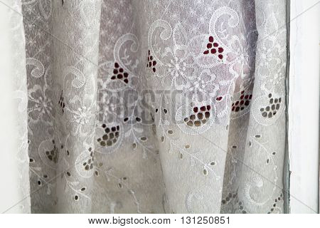 greyish curtain with hole embroidery in an old window background texture with copy space selected focus