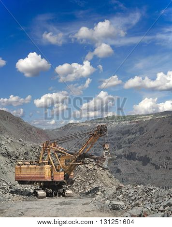 Large excavator on the iron ore opencast on sunny day