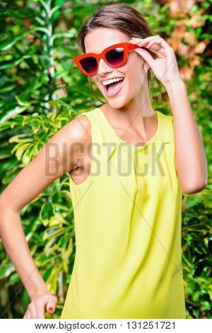 Pretty smiling woman in bright yellow dress and pin-up glasses enjoying summer. Beauty, fashion.