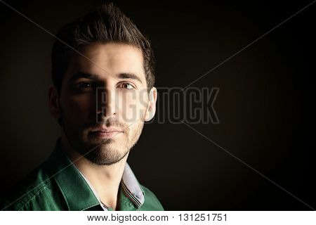 Close-up portrait of a handsome young man looking at camera and slightly smiling. Men's beauty. Studio shot over black background.