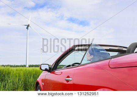 Woman in a red cabriolet in a field with wind power. Travel concept.