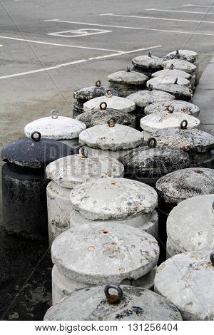 Concrete bollards on city pavement with road markings