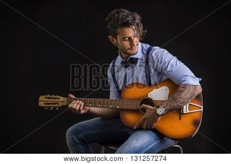 Portrait of hipster playing guitar against black background, in studio shot