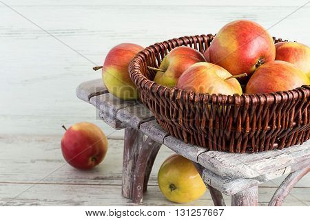 Apples in a wicker basket on a bench on a light wooden background.