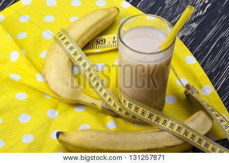 Banana juice with bananas and measuring tape on the wooden background
