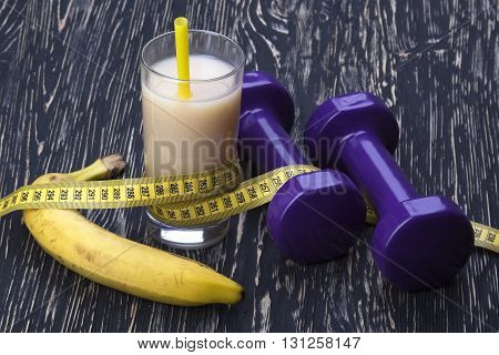banana, juice, measurement tape and dumbbells on wooden table