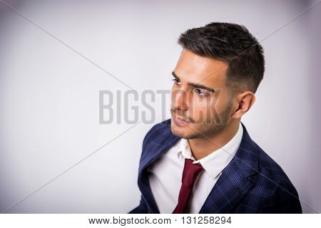 Handsome young man in blue business jacket and jeans posing on light background in studio