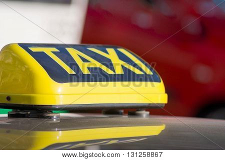 the big yellow sign or symbol with a taxi inscription a closeup is located on a roof of the car and a blank space