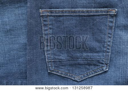 fragment of trousers from jeans material or jeans clothes with the big sewn pocket closeup for the textile textured background of blue color
