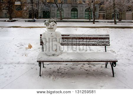 Snowman sitting on the bench in the city