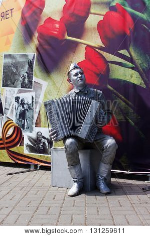 VOLGOGRAD RUSSIA - May 04 2016: A live sculpture of the Soviet soldier of the player on an accordion against a card with flowers. Volgograd Russia