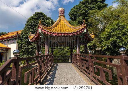 A bridge and walkway leading to the entrance of a Chinese Pagoda