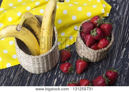 strawberries and bananas in a basket on the wooden desk
