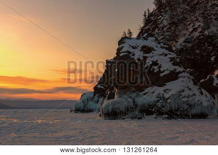 Dawn and the rock near island Lohmaty. Beautiful winter landscape in the Lake Baikal.
