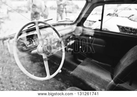 Interior And Steering Wheel On Old Vintage Retro Car. Black And White Photo