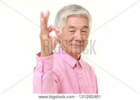 senior Japanese man showing perfect sign on white background
