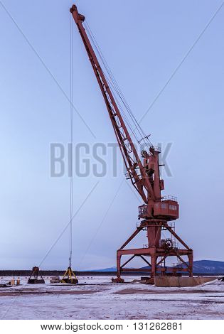 Ships cargo cranes on the shore of Lake Baikal in winter.