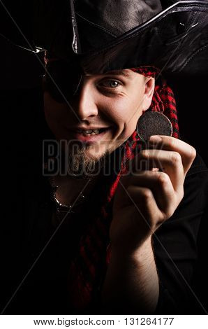 Portrait of a smirking man-pirate, looking at the old coin in hand