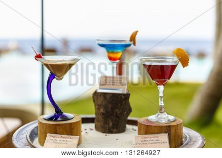 Glasses Of Color Cocktails On Pool Background