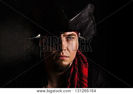 Portrait of a young pirate with a focused eye on a black background