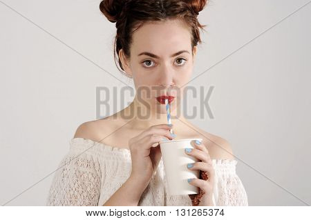 Lovely young girl is drinking with a straw. studio shot with light background.