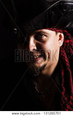 Portrait of a young male pirate with an angry face on a black background