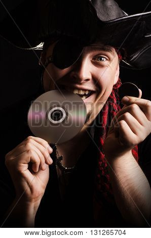 Portrait of a young male pirate with a smile biting CD as checking the quality of old gold coins