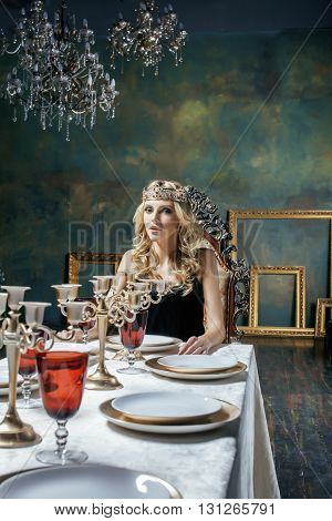 young blond woman wearing crown in fairy luxury interior with empty antique frames total wealth, magic rich concept