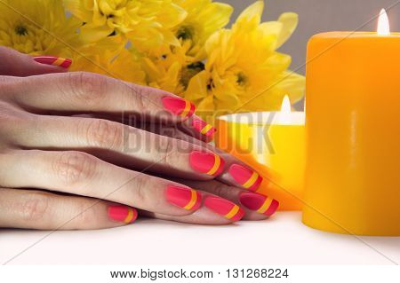 Skin care of a beauty female hands with pink and yellow striped nail art manicure. And yellow chrysanthemums with yellow two candles on the background