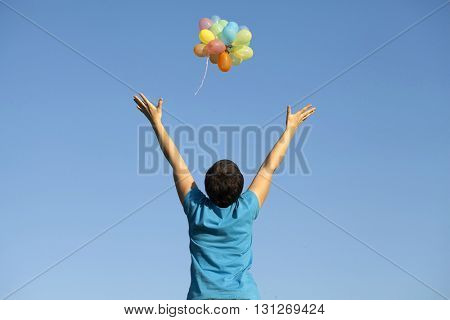 Young woman with colorful balloons over blue sky