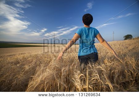 Young woman enjoying nature and sunlight in wheat field at sunset