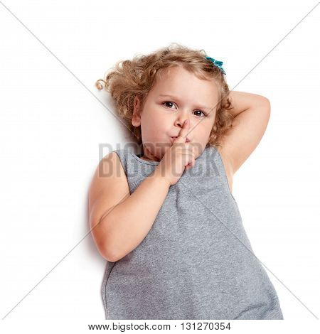 Young little girl with curly hair in gray dress lying and doing shh silence sign over isolated white background