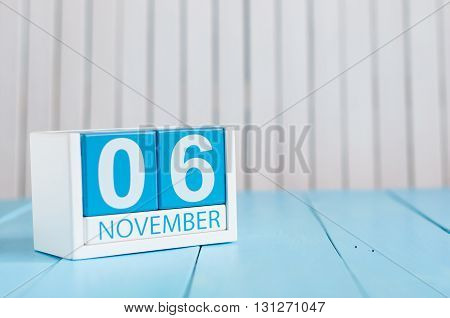 November 6th. Image of november 6 wooden color calendar on blue background. Autumn day. Empty space for text.