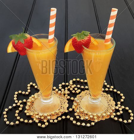 Orange fruit juice drink in glasses on gold doilies with fresh strawberries, striped straws and gold bead decorations over dark wood background. High in vitamins and antioxidants.