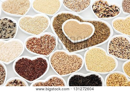 Healthy grain food selection in heart shaped porcelain bowls over white background.