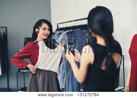 Girl posing with dress in the store when friend photographing her
