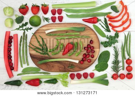 Health and super food of red and green fruit and vegetables on a maple wood board over white distressed background. High in vitamins, antioxidants, minerals and anthocyanins.