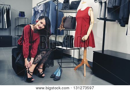 Attractive Vietnamese girl trying on heels from new collection