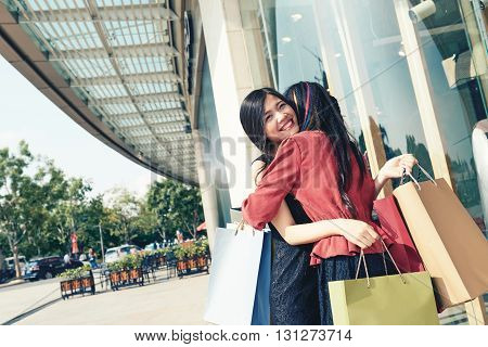 Happy female friends hugging in front of shopping mall