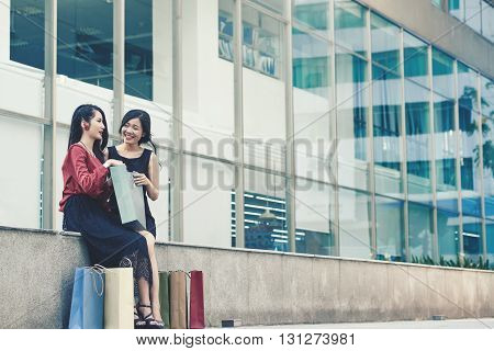 Beautiful Vietnamese young women with many shopping bags sitting outdoors