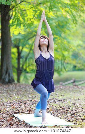 Japanese woman outside doing yoga warrior I pose