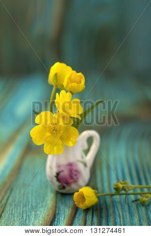 Ranunculus bouquet in miniature, diminutive jug. Macro close-up photo with soft focus, bouquet of buttercup flowers. Rustic colored wooden background