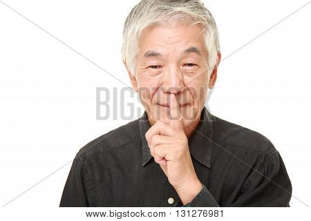 studio shot of senior Japanese man whith silence gestures on white background